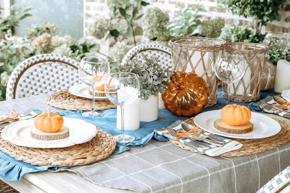 Blue and orange fall table decor. Mini orange pumpkins, white plates, lanterns and candles. #ABlissfulNest #fallinspiration #falldecor #Thanksgiving