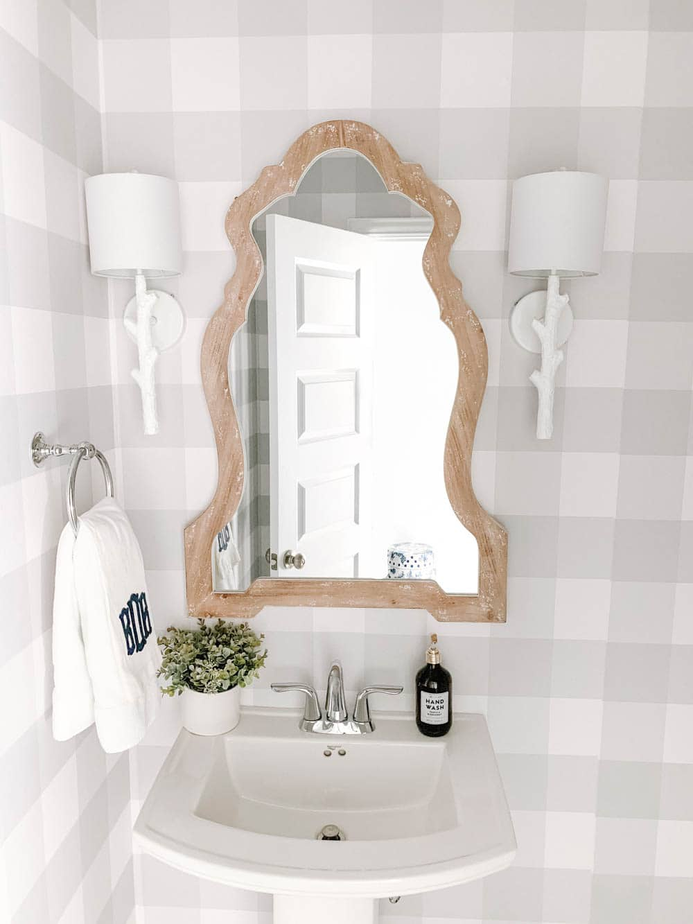 Wood mirror, white faux bois sconces and grey and white buffalo check wallpaper in this coastal bathroom design. #ABlissfulNets #bathroom #farmhouse #bathroomdesign