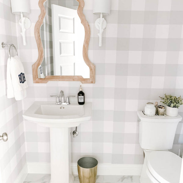 This farmhouse bathroom features grey and white buffalo check wallpaper, gold accents and a white washed wood mirror. #ABlissfulNest #bathroom #bathroomdesign #farmhouse #powderbathroom