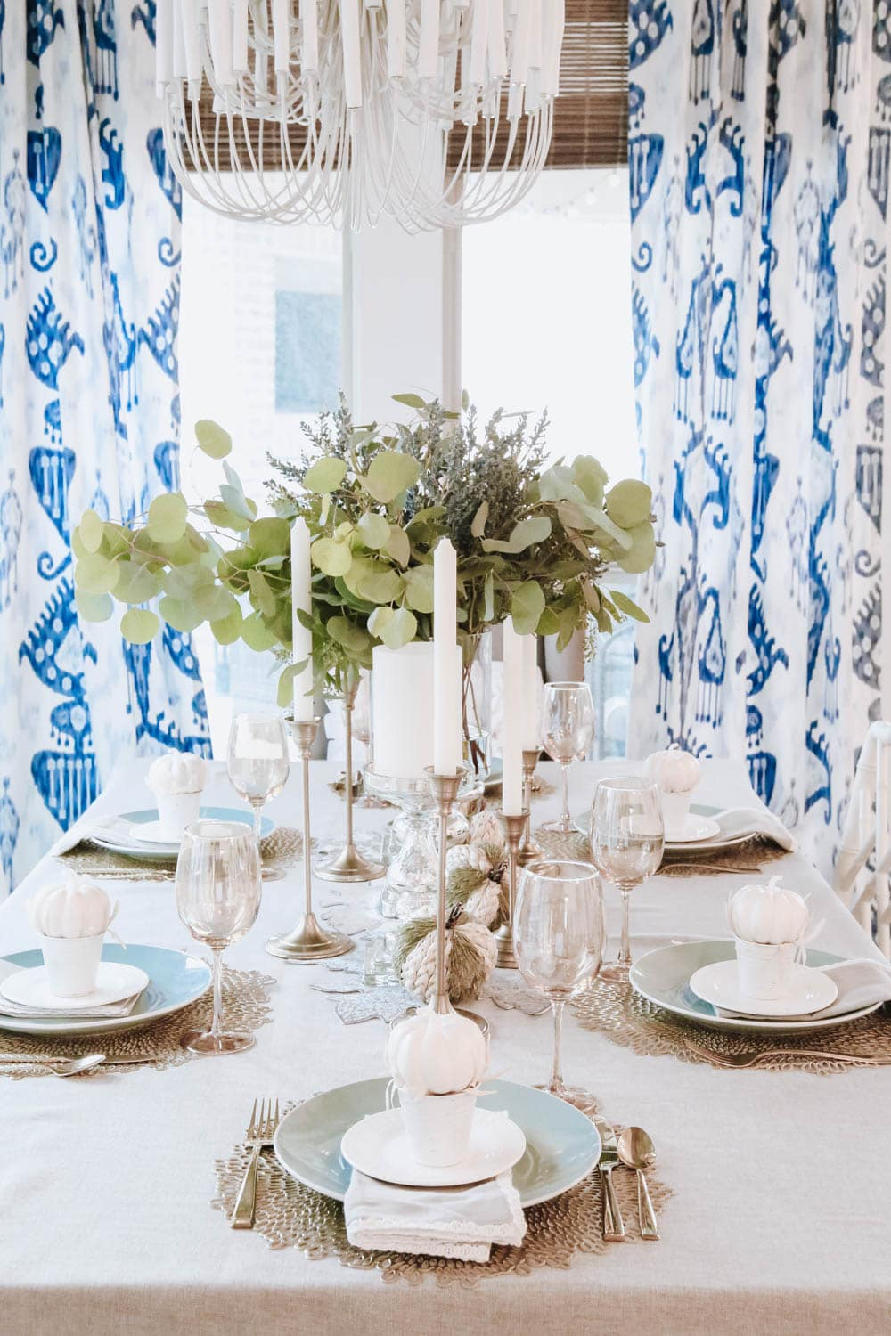Using white pumpkins, white plates and gold candle sticks, gold flatware and more, gives a subtle glam look to this fall tablescape. #ABlissfulNest #falltable #thanksgiving