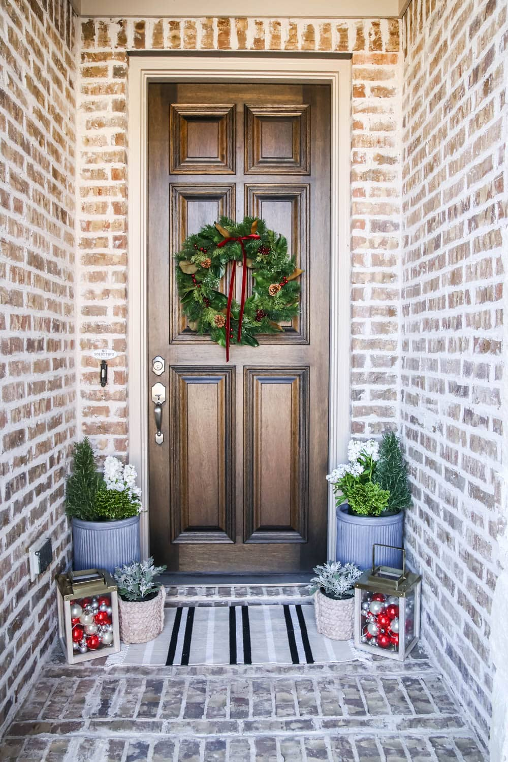 A traditional Christmas porch in red and green with gold lanterns, Christmas ornaments and fresh flowers. #ABlissfulNest #christmasporch #christmasdecorating