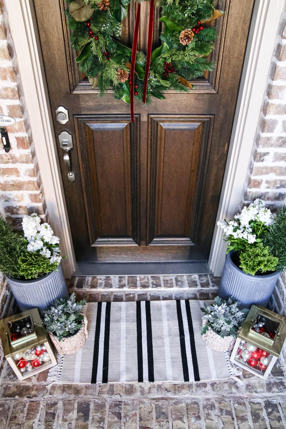 A striped door mat adds a fun pop to this Christmas porch. #ABlissfulNest #christmasporch #christmasdecor