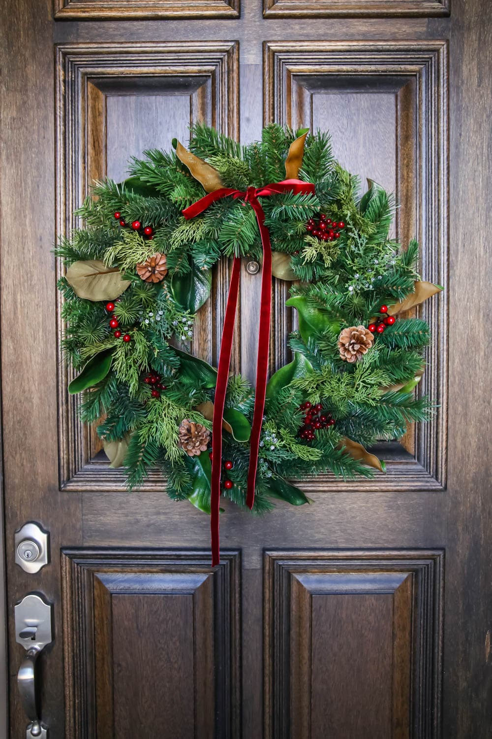 A beautiful traditional wreath with a velvet red ribbon, pincones and magnolia leaves. #ABlissfulNest #christmasporch #christmasdecorating