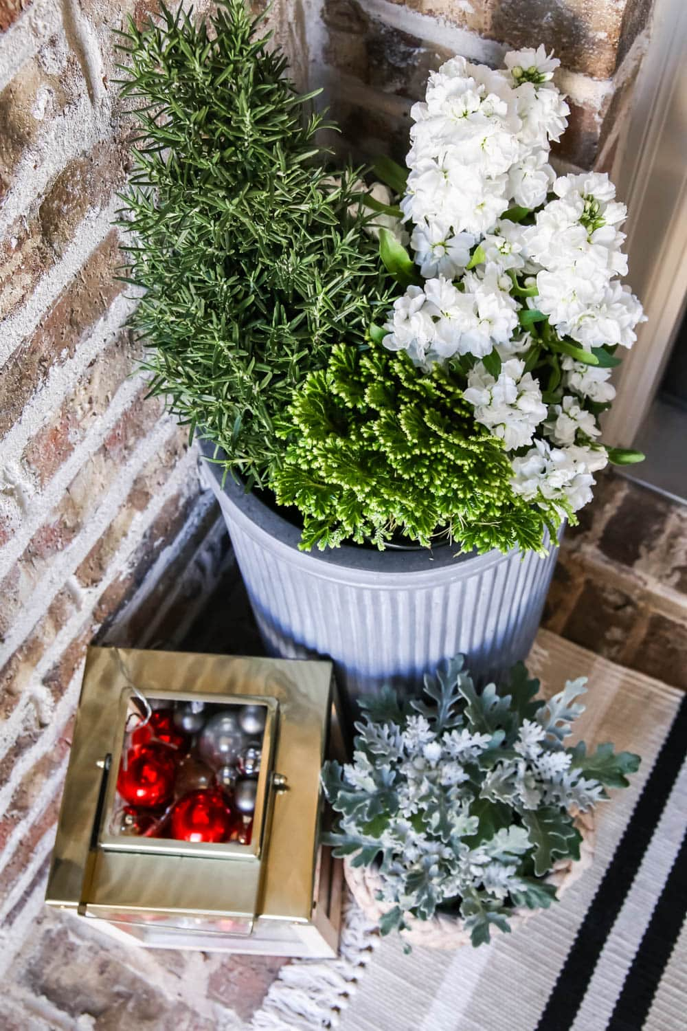 Gold lantern filled with Christmas ornaments, fresh winter flowers and a striped doormat. #ABlissfulNest #christmasporch #christmasdecor