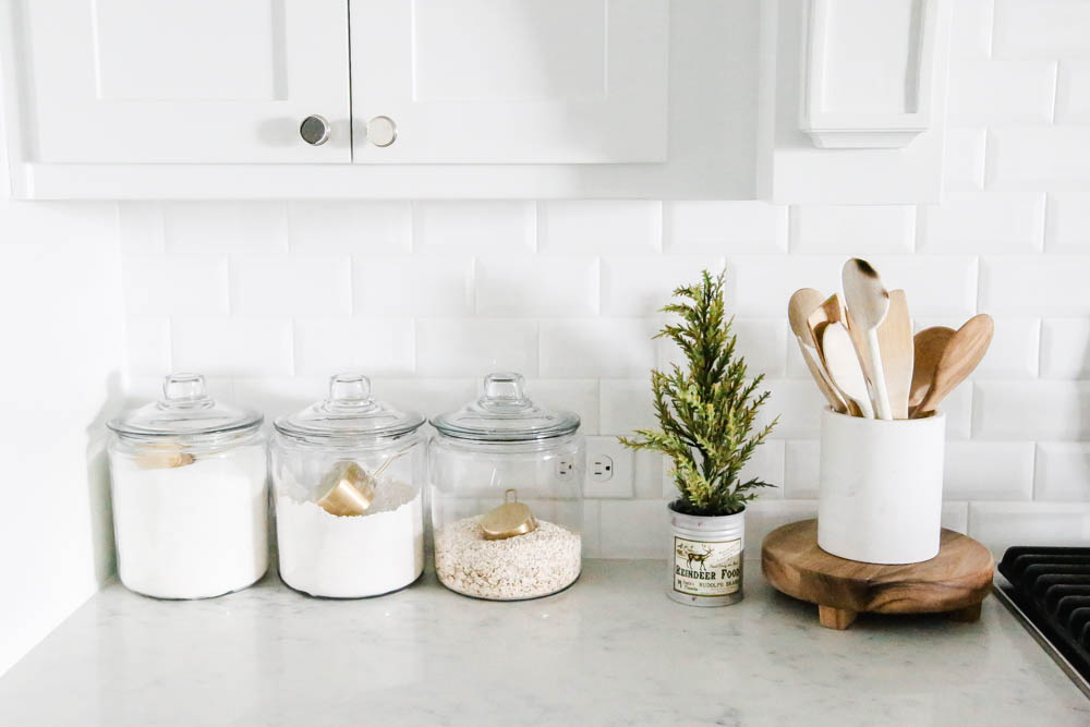 Christmas decor in a bright white kitchen. Baking canisters on Carrara counter. #ABlissfulNest #Christmaskitchen #whitekitchen