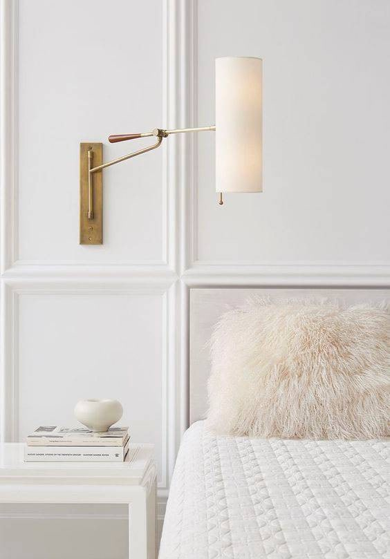 Layered all-white bedroom with side table and wall light