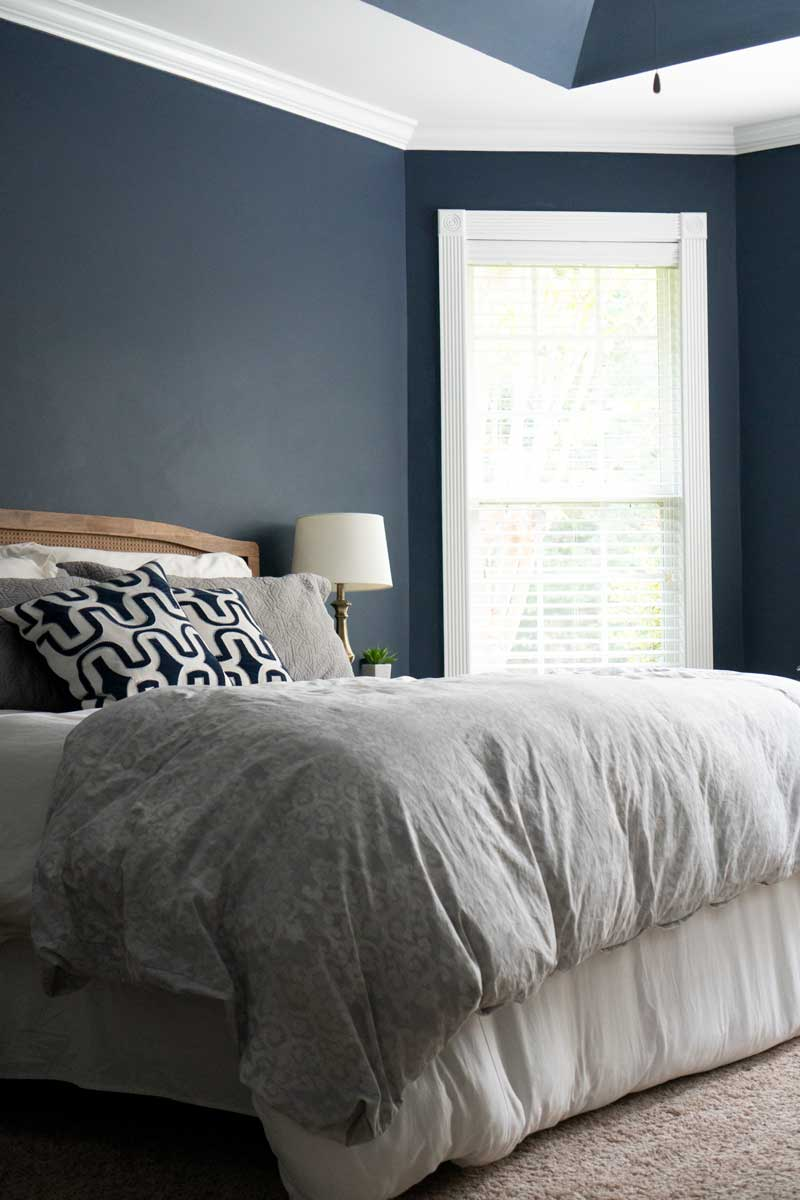 Bedroom painted in Sherwin Williams naval, one of the top paint colors of 2020
