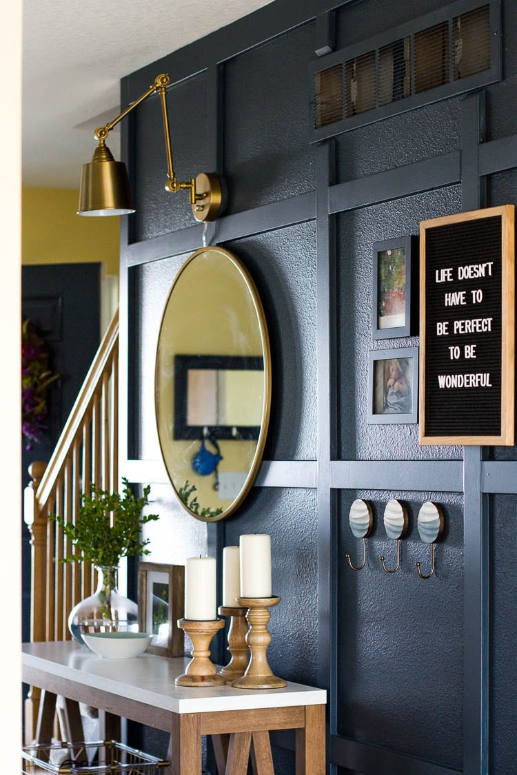 navy entryway with mirror and painted air ducts that are clean