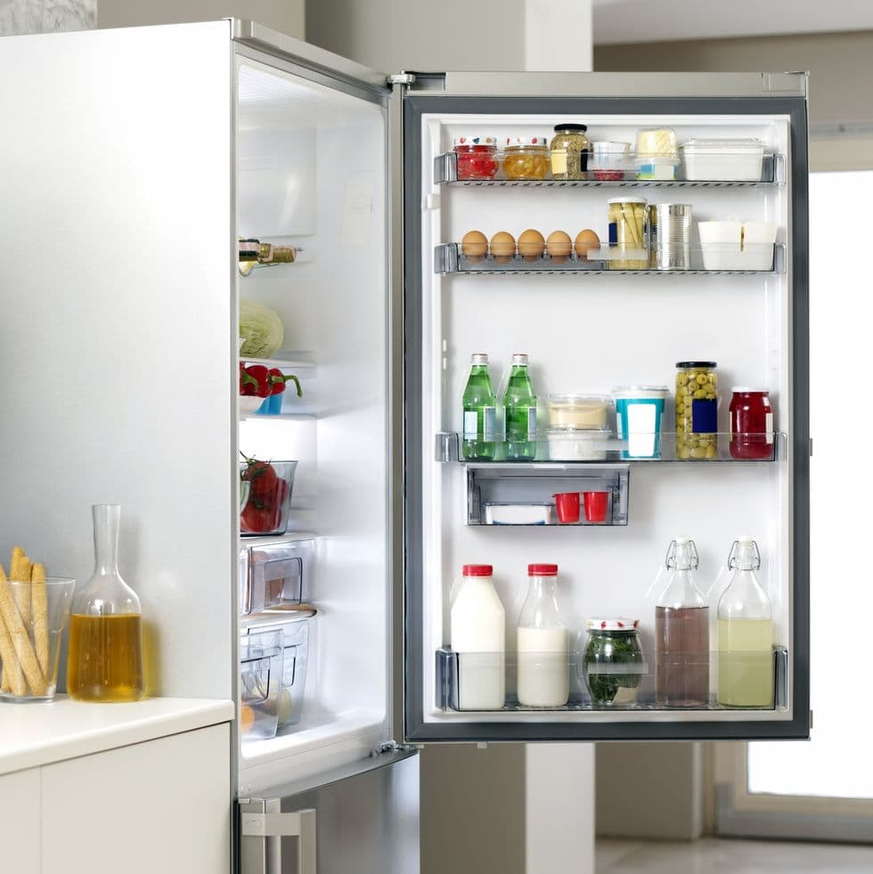 Clean fridge with an open door showing organized food items