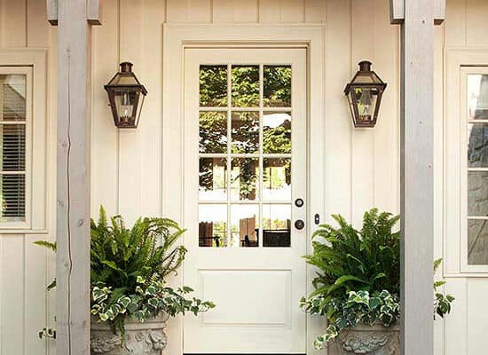 White home with two matching planters on either side of the door, both containing ferns.
