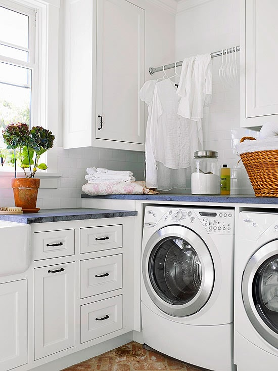 Clean laundry room with sunny window and dark countertops