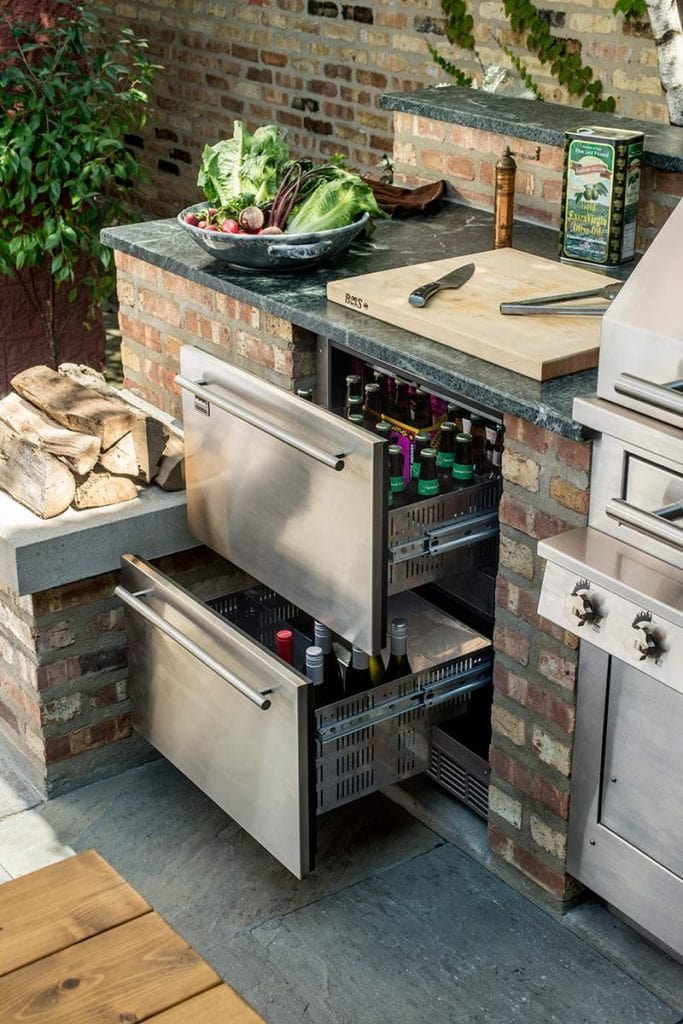 outdoor kitchen bar built with brick and stainless steel drawers and grill