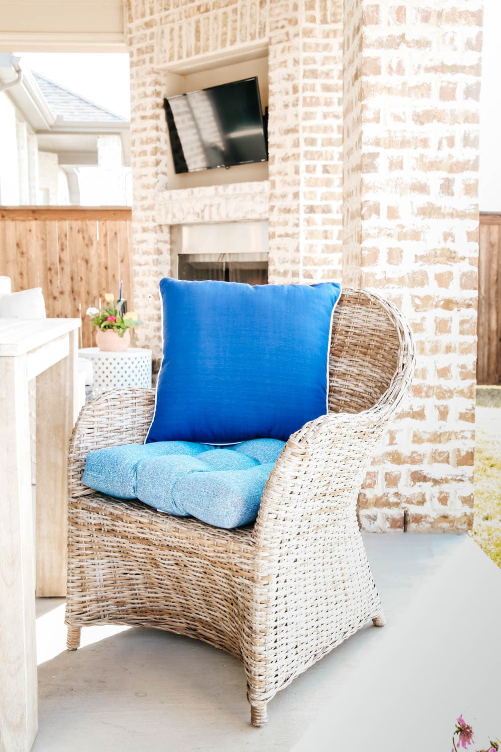 blue cushions, wicker chairs, brick fireplace, spring patio decor. #ABlissfulNest #patio #outdoor #backyard