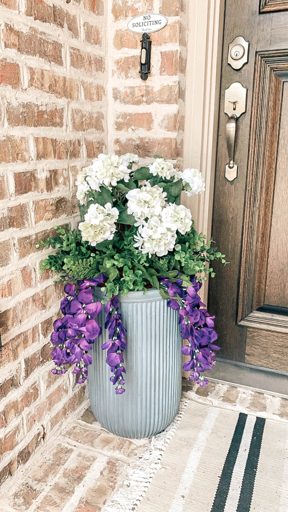 Outdoor planter on front porch filled with faux UV protected faux flowers. #outdoor #planterideas #planters #ABlissfulNest