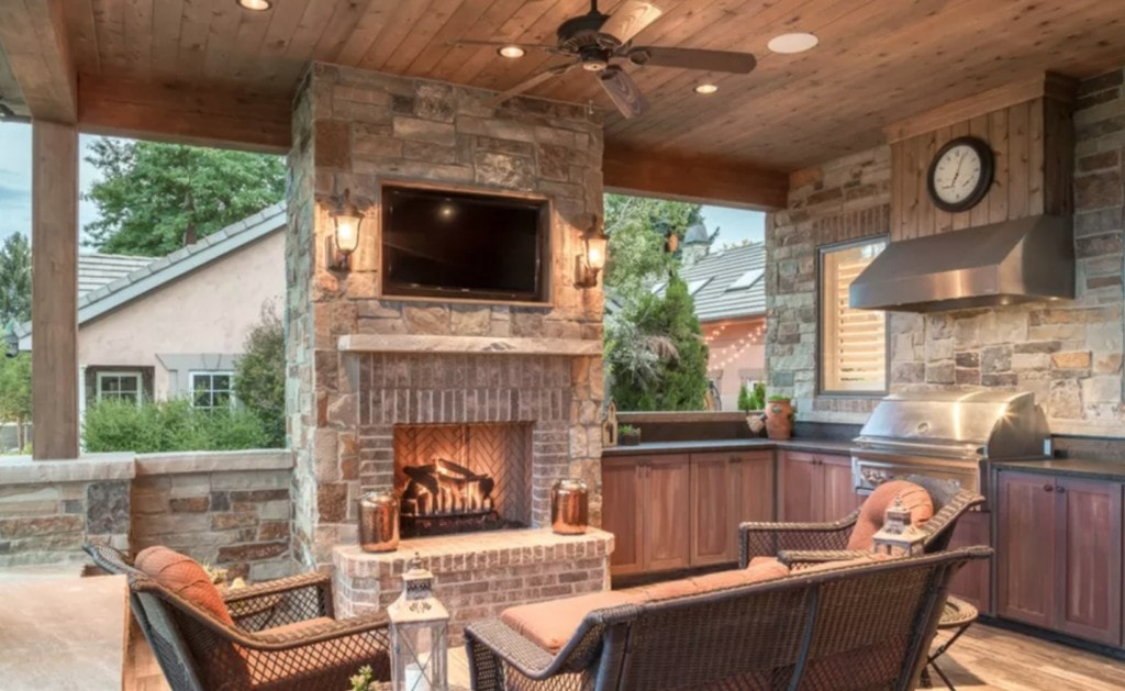 outdoor bar ideas showcased next to a stone fireplace