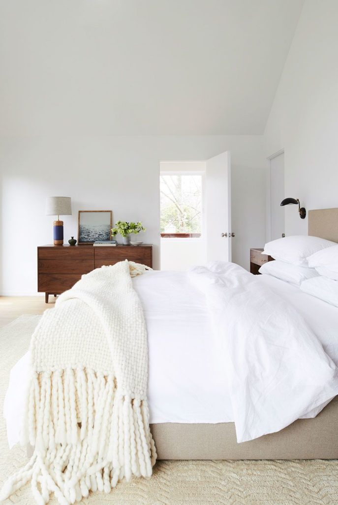 Room with layered tones of white such as white walls, bedding and throw blanket