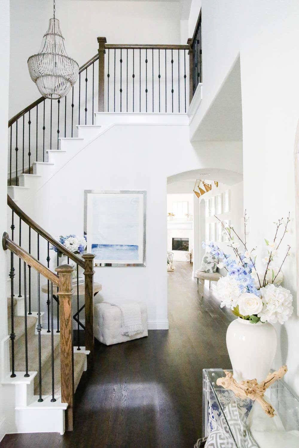 Entryway view with blue and white decor, ocean art, beaded chandelier, flowers in white vase, white painted interior. #ABlissfulNest #entrydecor #entryway #designtips