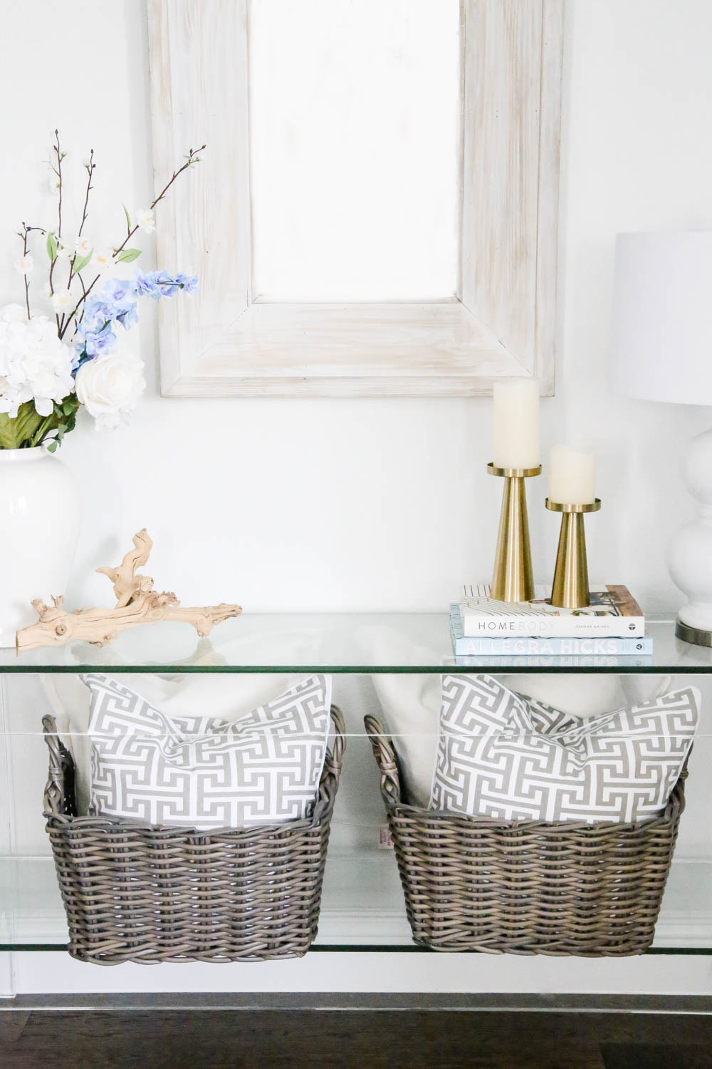 Baskets filled with pillows, spring flowers, gold candlesticks on a lucite table. #ABlissfulNest #springdecor #homedecor #decorideas