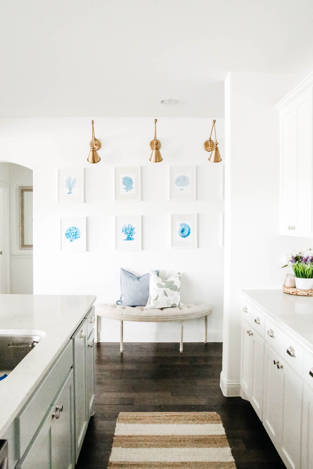 Gallery wall details in a white kitchen. Blue and white coastal art prints. #gallerywall #designtips #kitcheninspo #ABlissfulNest