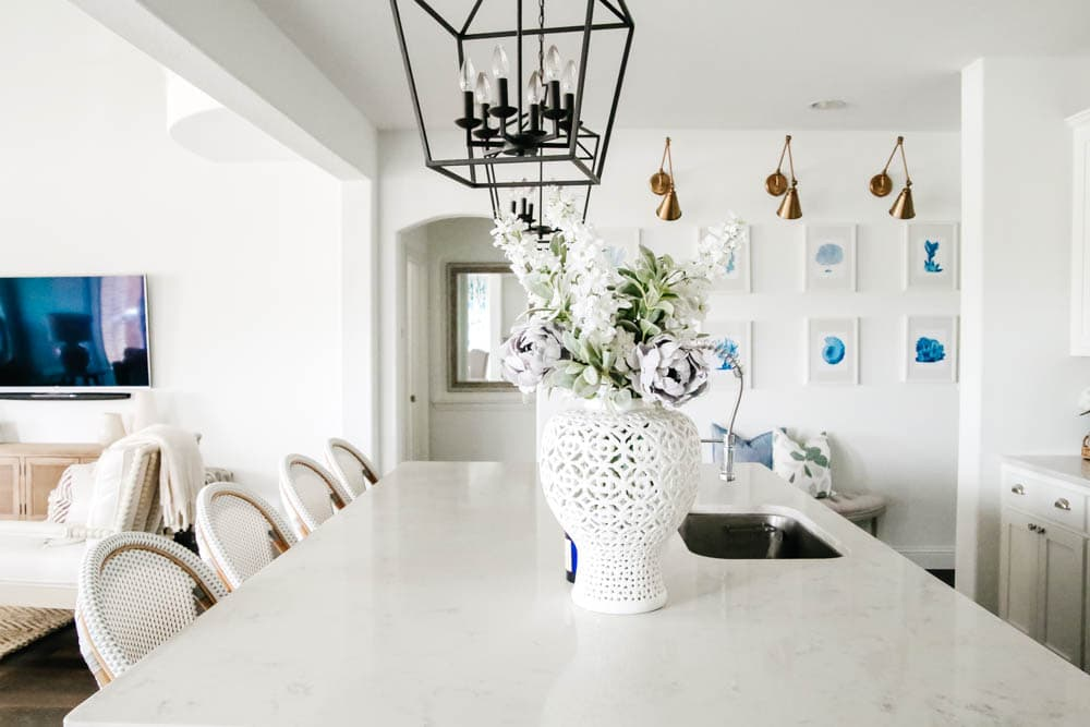 White kitchen with blue painted island. Rattan bistro chairs, black lanterns, carrara quartz counters. #ABlissfulNest #whitekitchen #springhometour
