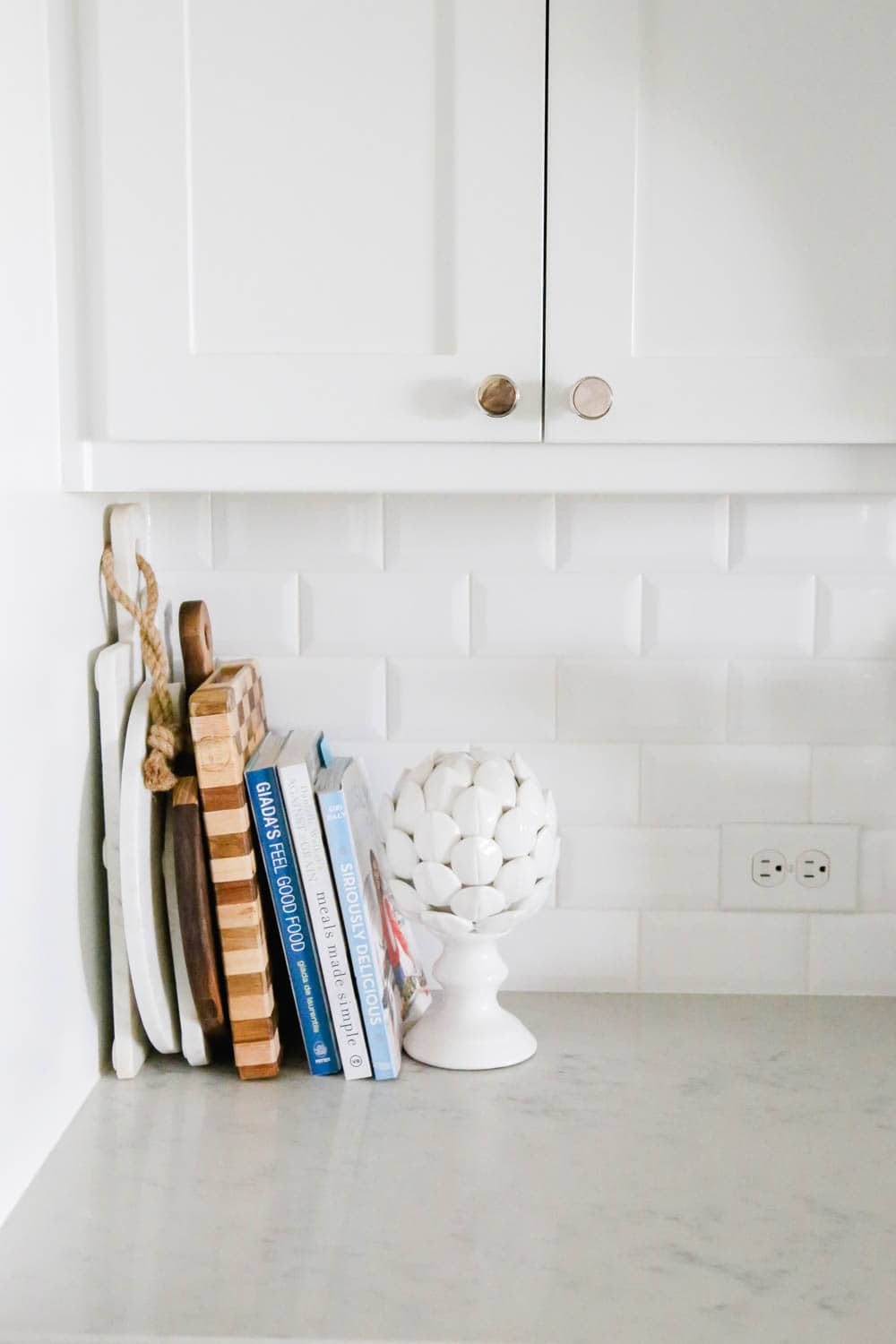 Kitchen counter decorating with cookbooks and cutting boards. #whitekitchen #kitcheninspo #kitchendecor #ABlissfulNest