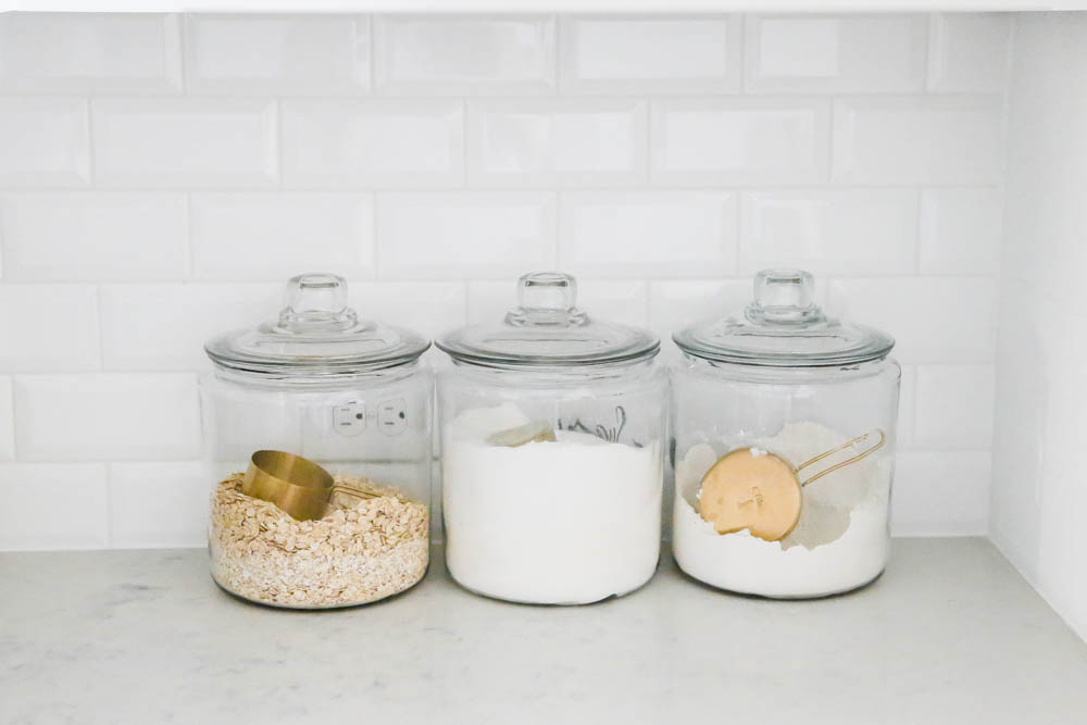 Glass canisters to hold baking essentials with gold measuring cups. #whitekitchen #kitcheninspo #kitchendecor #ABlissfulNest