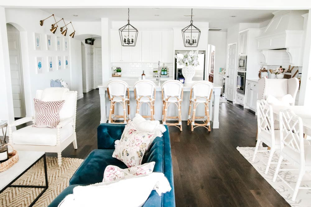 Bright white walls with blue home decor, navy velvet sofa, french bistro barstools, white kitchen with soft texture accents. #ABlissfulNest #whitekitchen #whiteinterior #designtips #kitchen