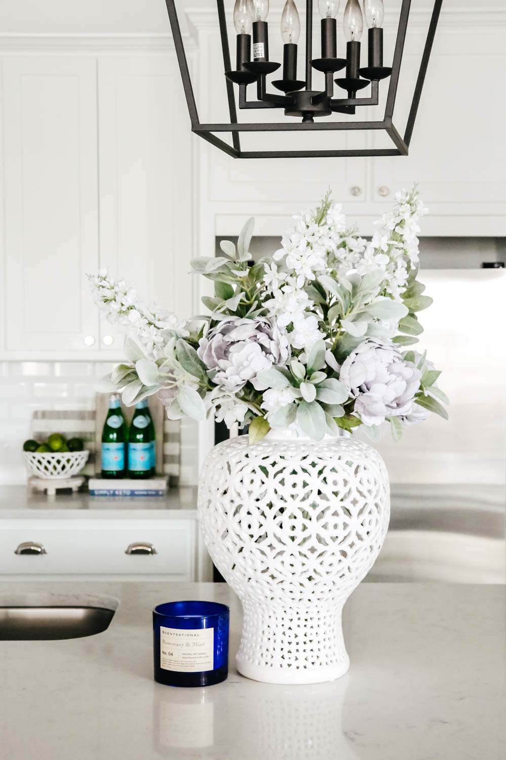 White lattice vase with flowers on white counter top. #whitekitchen #kitchendecor #kitchenideas #ABlissfulNest
