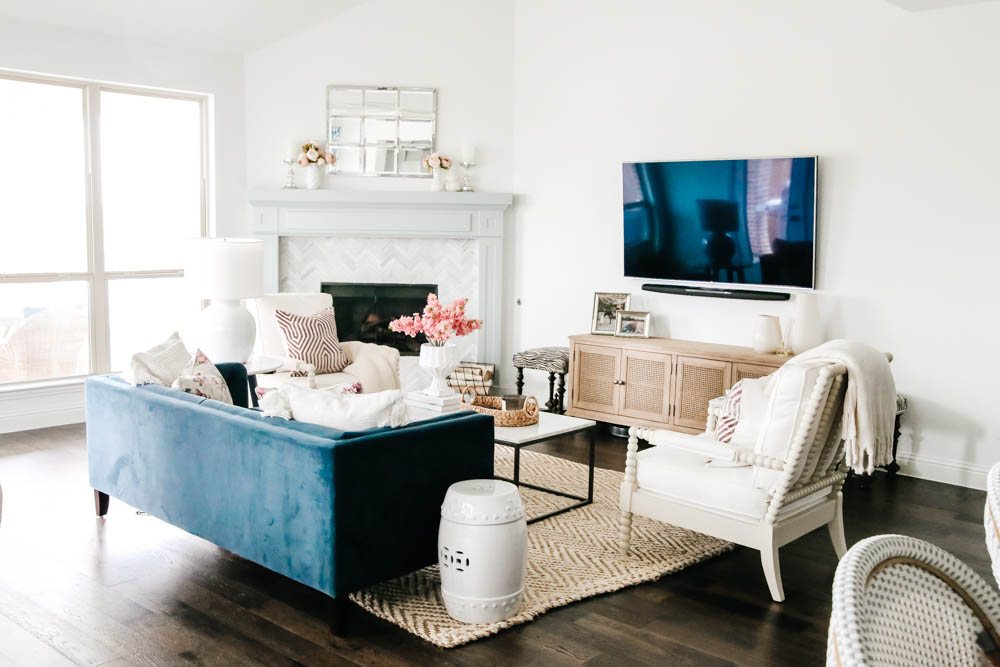 Living room with navy velvet sofa, bright white walls and soft lavender and pink touches. #springdecor #hometour #livingroom #ABlissfulNest