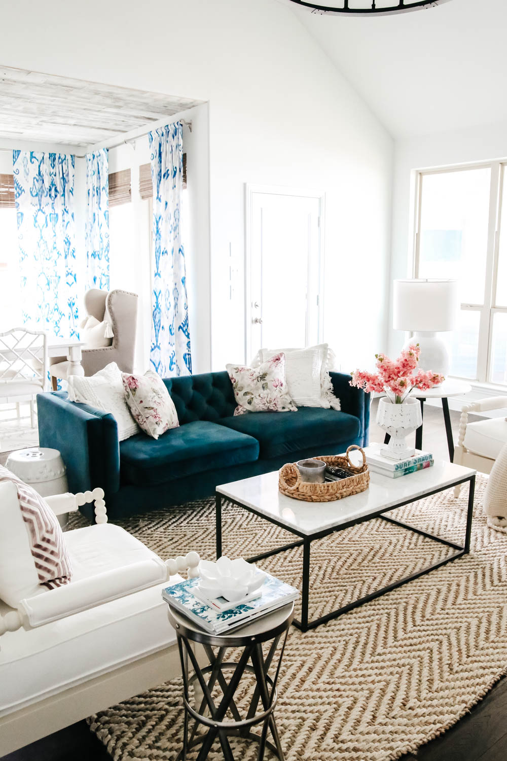 Navy blue sofa, marble and iron coffee table, white painted walls, blue and white decor accents with pops of lavender. #livingroominspo #springdecor #homedecor #ABlissfulNest