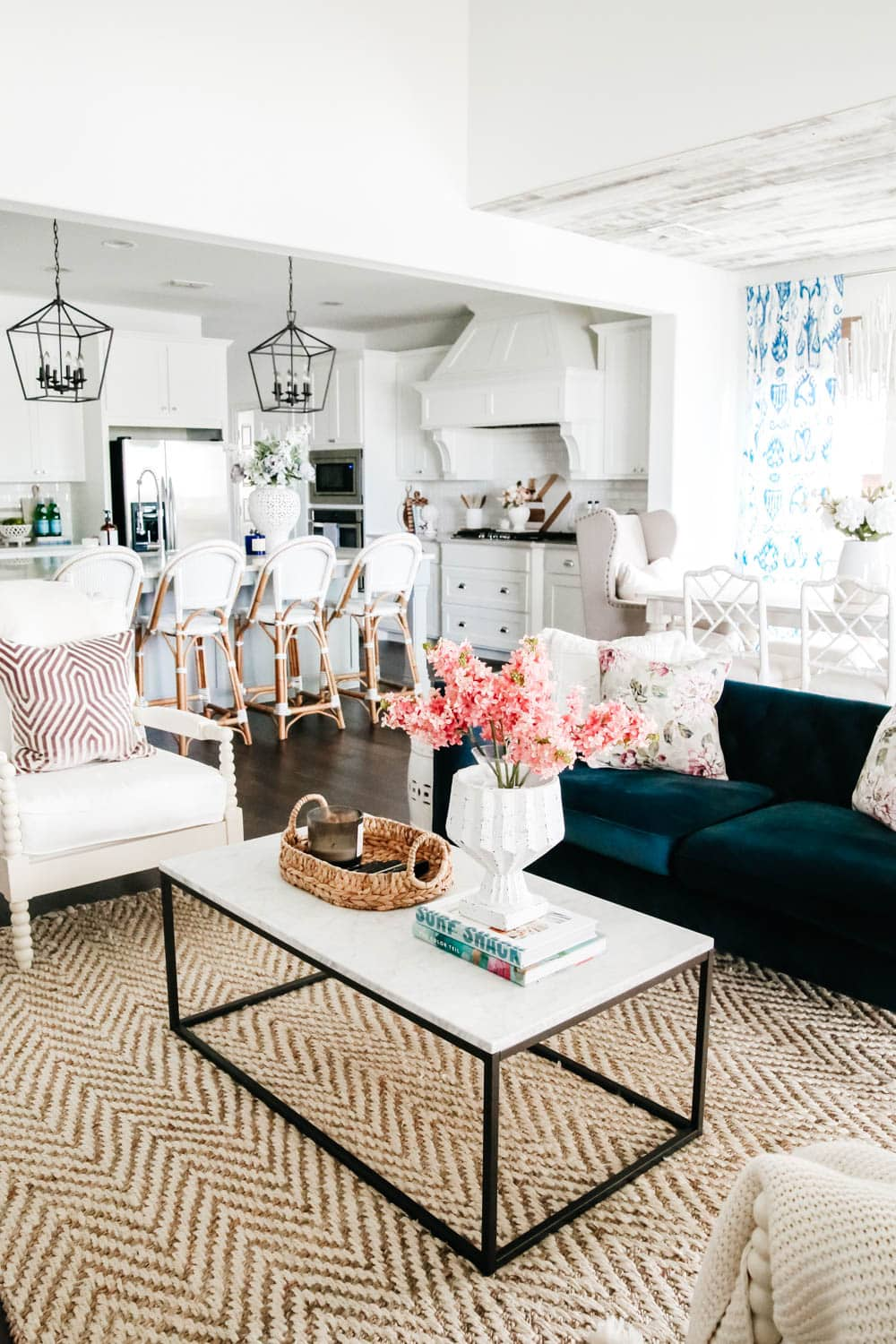 Living room with navy blue sofa and white walls. Blue and white home decor accents with pops of pink and lavender. #livingroom #livingroominspo #hometour #ABlissfulNest