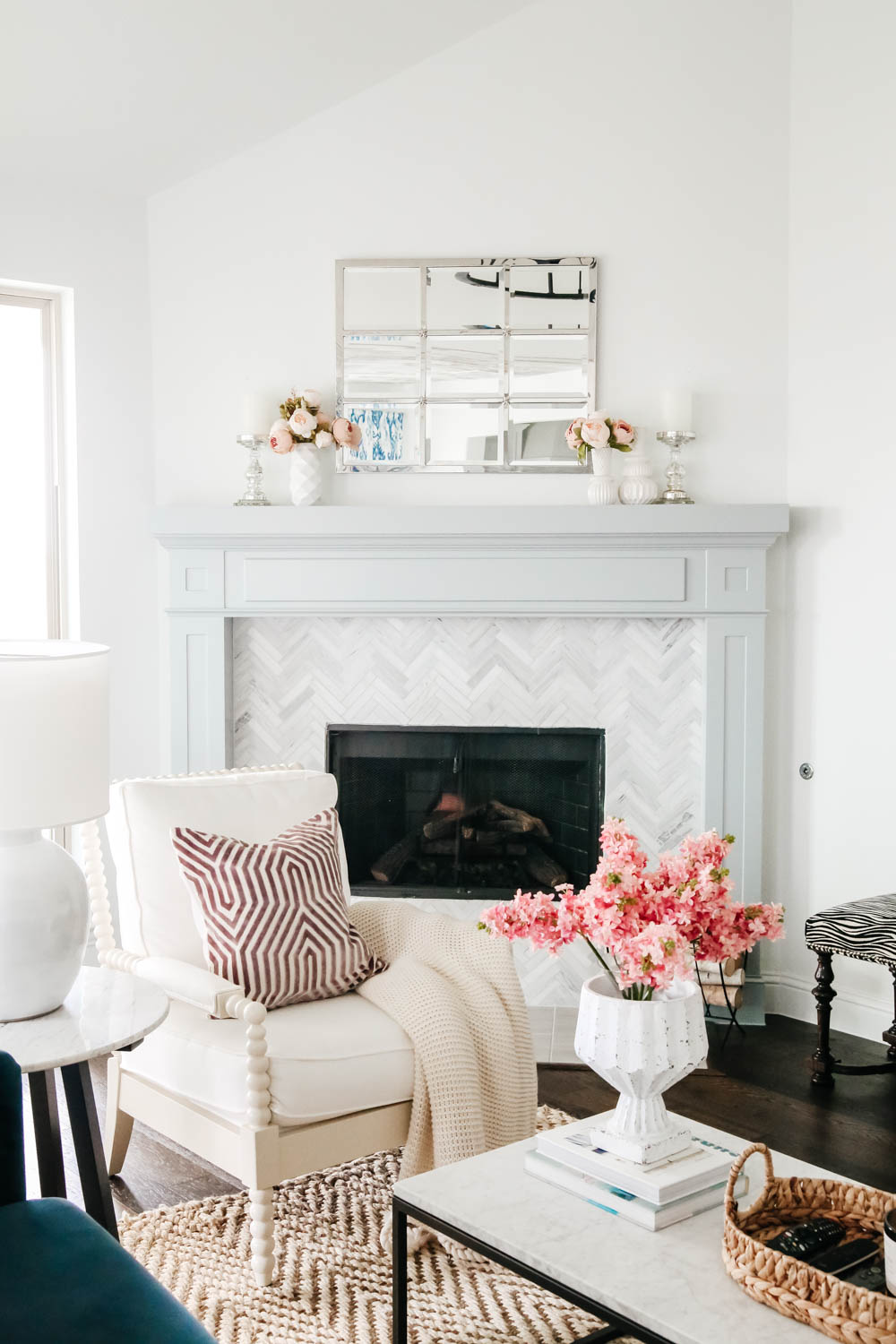 Light grey blue painted fireplace mantle with white spindle chair and lavender home decor accents. #livingroominspo #hometour #fireplacemantle #springhometour #ABlissfulNest