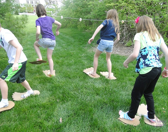 kids walking through the grass wearing giant cardboard foot cutouts on their feet