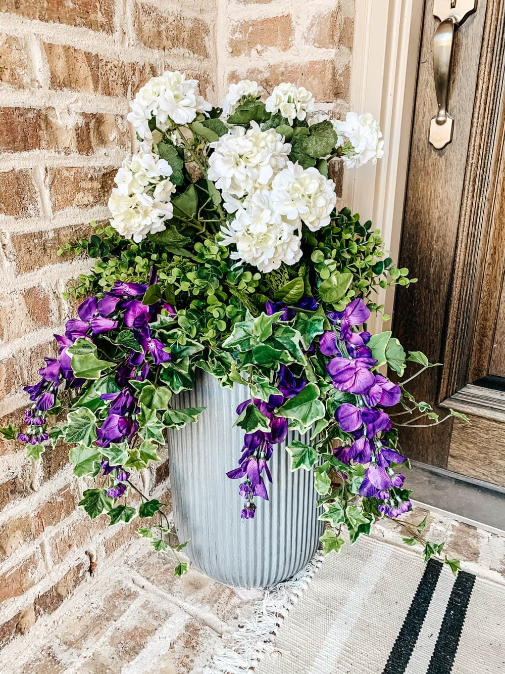 This planter is filled with UV protected artificial flowers and plants to create a stunning display. #ABlissfulNest #outdoorplanter #outdoordecorating