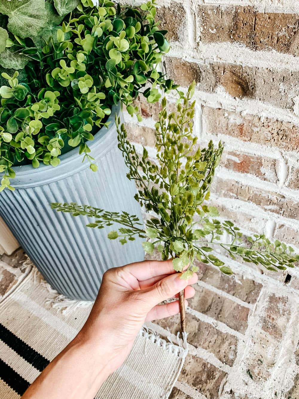 Using artificial plants and flowers outdoors for low-maintenance planter ideas. #ABlissfulNest #outdoorpatio #outdoorplanter
