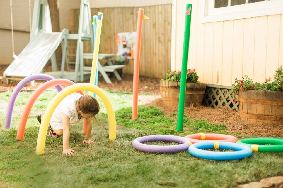 obstacle course made from pool noodles with a child crawling through