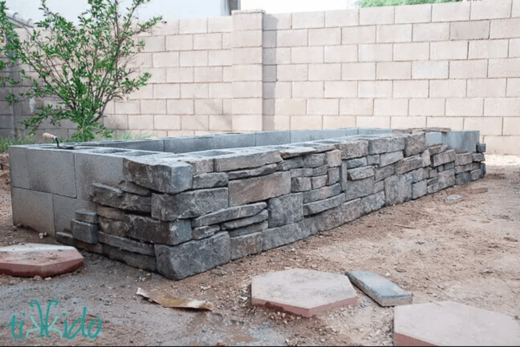 raised garden bed made from cinder blocks with stone veneer