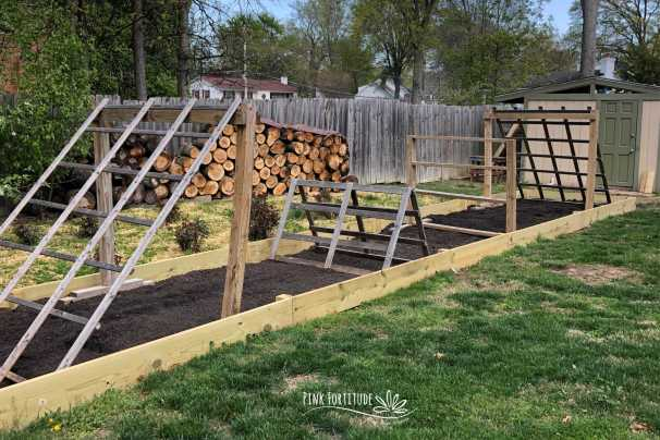 long raised garden bed with multiple trellises