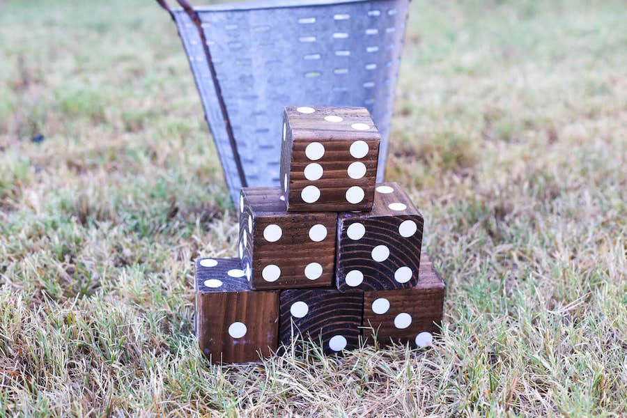 6 large wood dice in the grass with a metal bucket behind them
