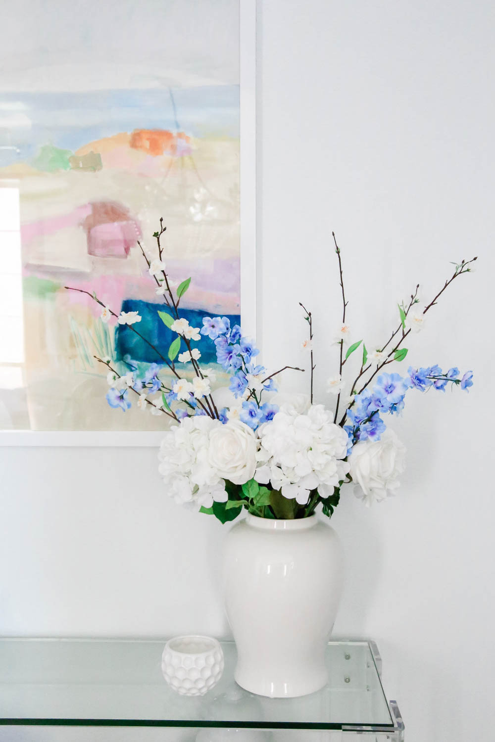 Simple faux flowers in blue and white add a summery touch to this entryway table. #entryway #summerdecor #ABlissfulNest