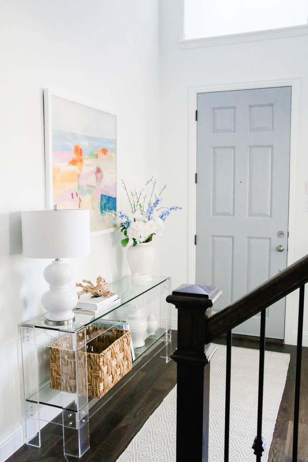 Blue front door in entryway with acrylic table, colorful modern art. #entryway #summerdecor #ABlissfulNest