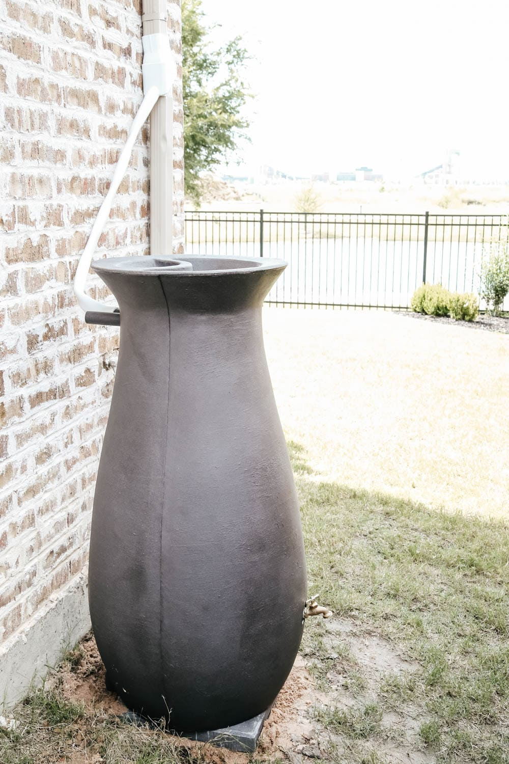 Install a rain barrel system for your home and save money and conserve your water supply. Simple step-by-step tutorial for installing a rain barrel. #ABlissfulNest
