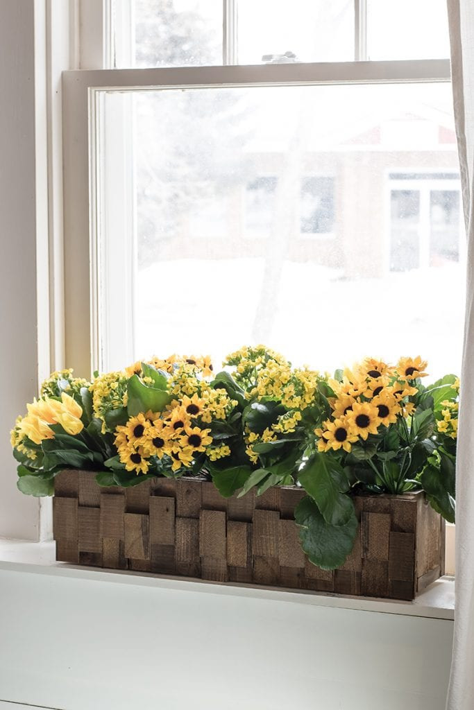 wood shim window planter box design filled with flowers
