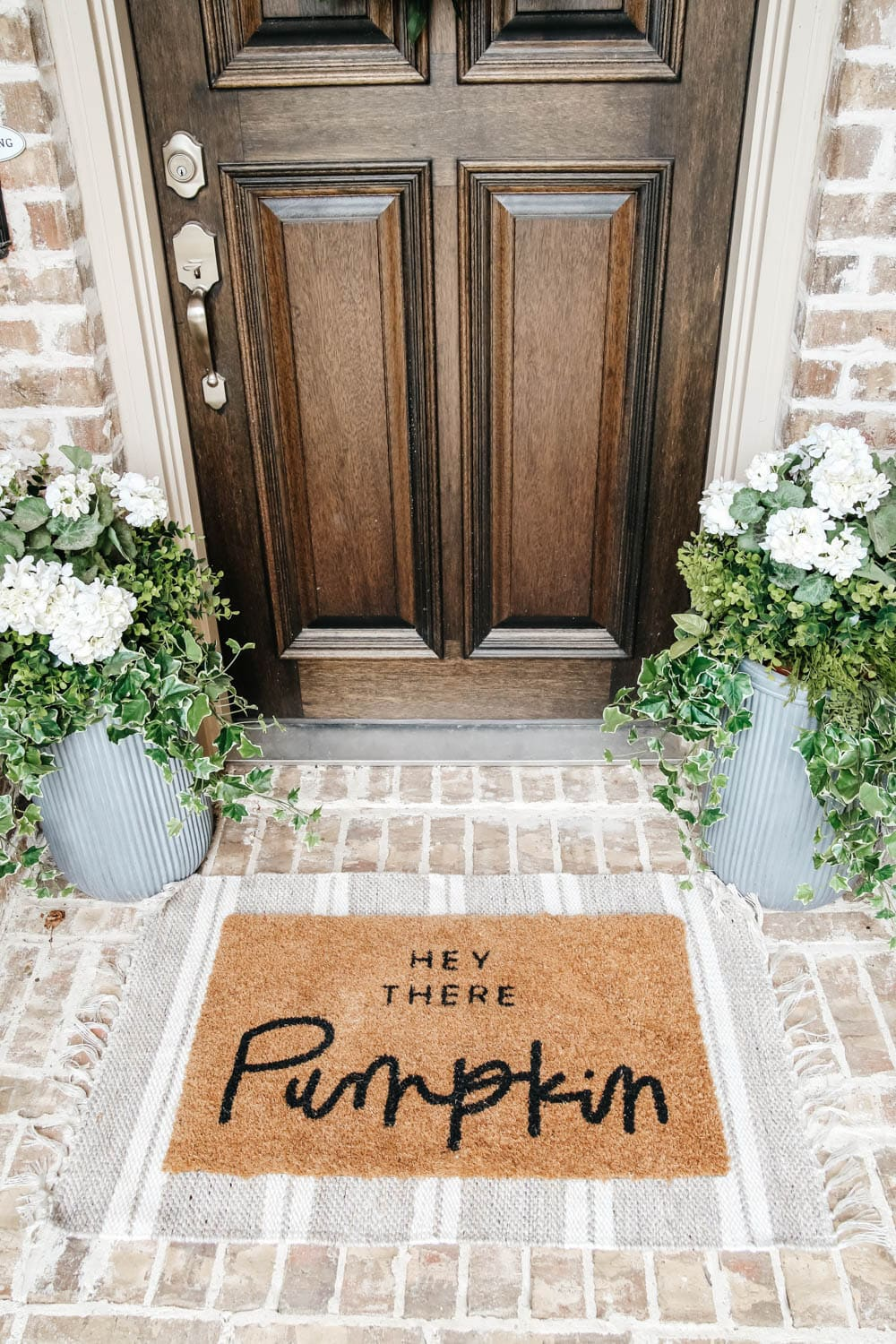 Layer your doormat with a patterned area rug for some contrast. #ABlissfulNest #fallporch