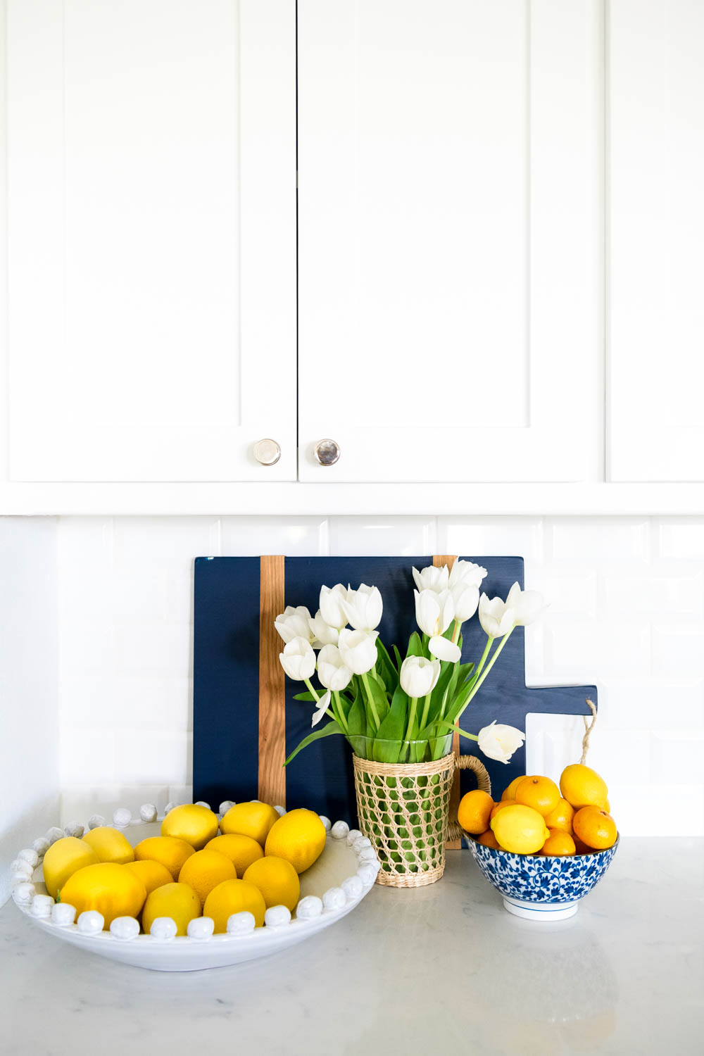 Add a bowl of fruit for color, blue and white bowl, tulips, cutting boards. #ABlissfulNest #kitchendecor #whitekitchen