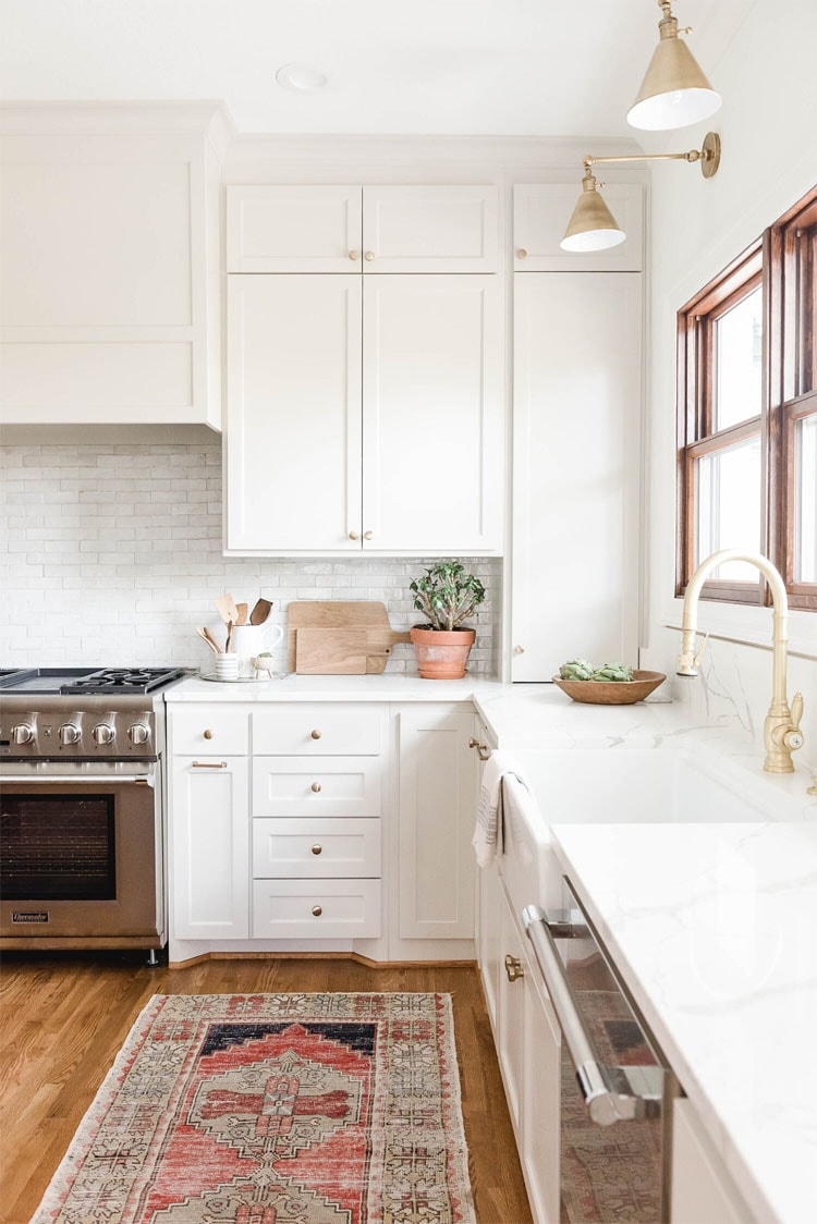 This gorgeous white and gold accented kitchen designed by High Street Homes is so beautiful!