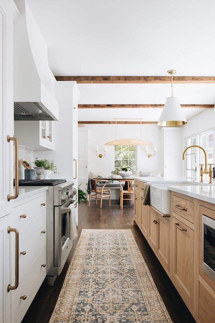 This gorgeous white and natural kitchen designed by Jean Stoffer Design has the most beautiful elements!