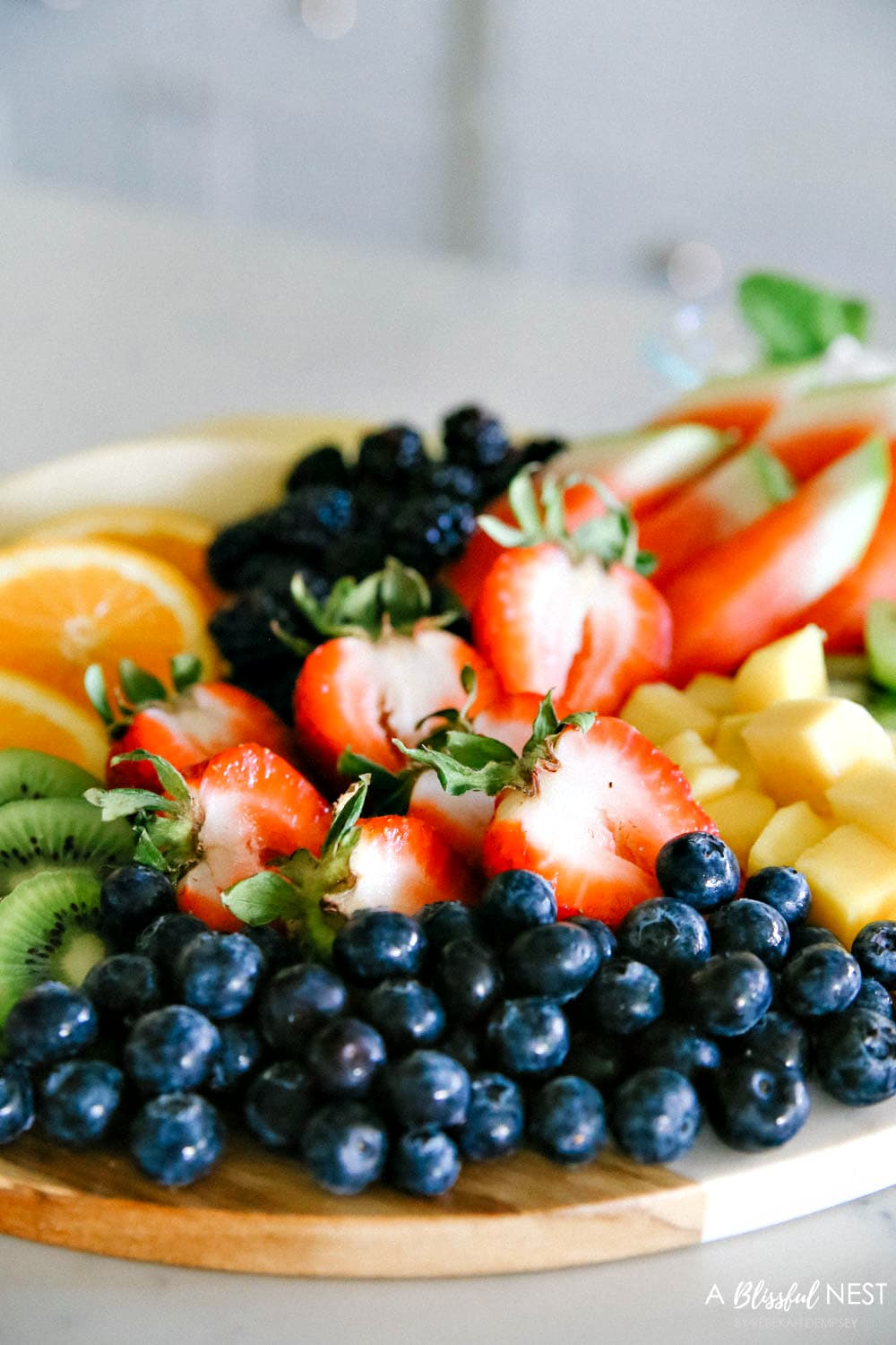 This beautiful fruit charcuterie board is so good to make on the weekends, for brunch, as an appetizer, and use all your favorite colorful fruits. #ABlissfulNest #charcuterieboard #fruitboard #fruitrecipe