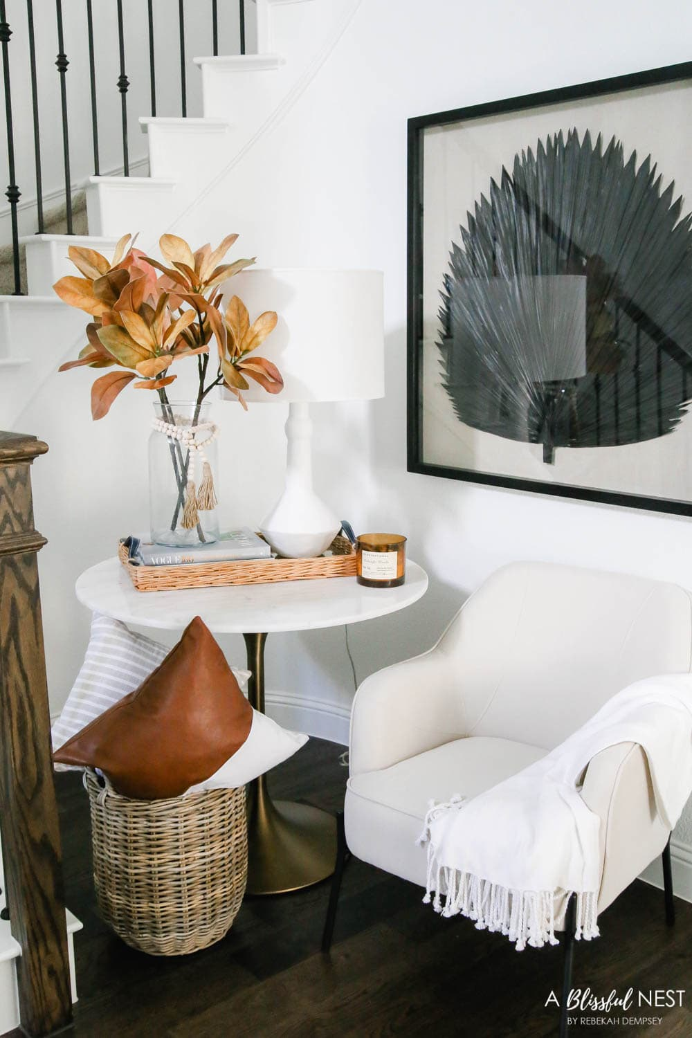 A cozy spot under the stairway. Fall florals, leather pillow, Sea Fan artwork. #ABlissfulNest #fallentry #falldecor