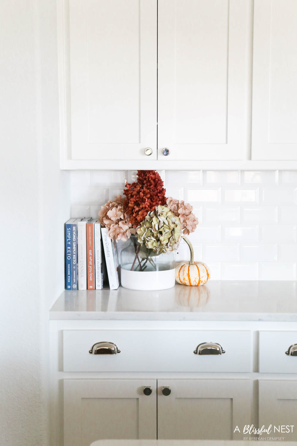 Beautiful fall decor details in this kitchen with burgundy eucalyptus leaves, delicious fall candles, Serena and Lily barstools. #ABlissfulNest #fallkitchen #falldecor #fallideas